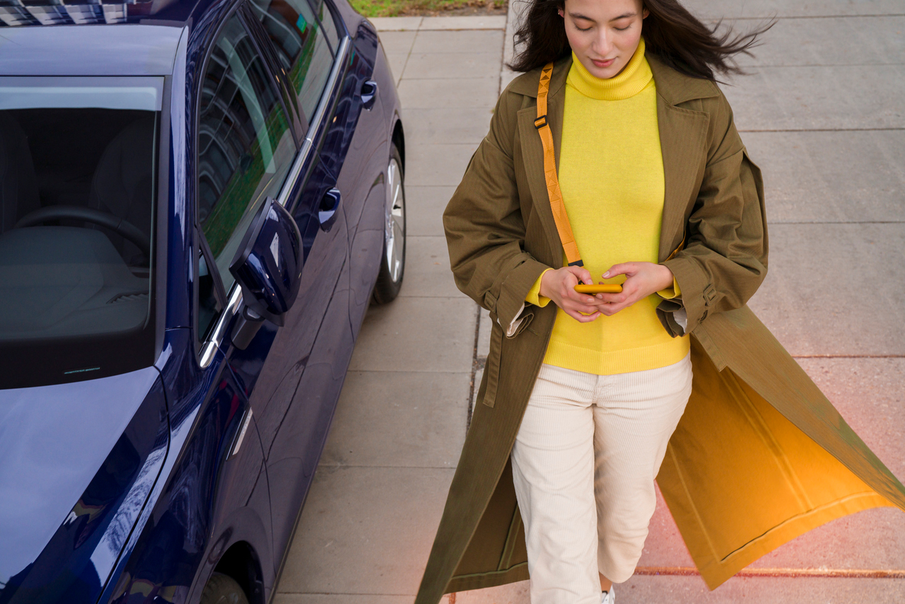 Woman in a yellow jumper and a phone in her hands walking past a blue car